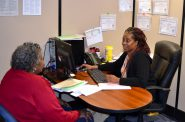 A volunteer for the Social Development Commission's tax preparation program meets with an individual. (Photo provided by SDC)