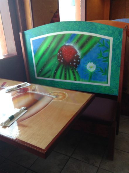 A small mural decorates the back of a bench in a booth. Photo by Cari Taylor-Carlson.