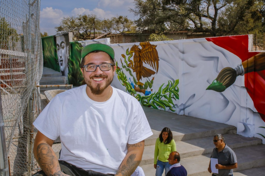 Chacho Lopez is all smiles as he sits in front of the completed mural. Photo by Rafael Montero.