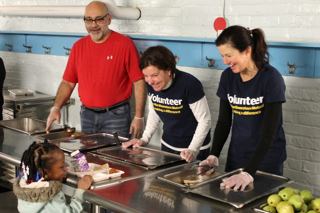 Chef Michael Feker and two volunteers from Northwestern Mutual serve a young student a hot breakfast. Photo by Mark Lisowski.