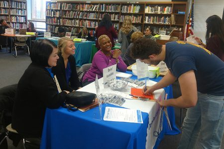 A student fills out an information form at the Dental Associates' booth at the Opportunity Fair. Photo courtesy of Carol Stein.