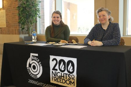 Madeline Krolczyk, a student assistant for university archives at Marquette, and Olga Schennikova, a Ph.D student at Marquette, help sign individuals up for their interviews. Photo by Margaret Cannon.