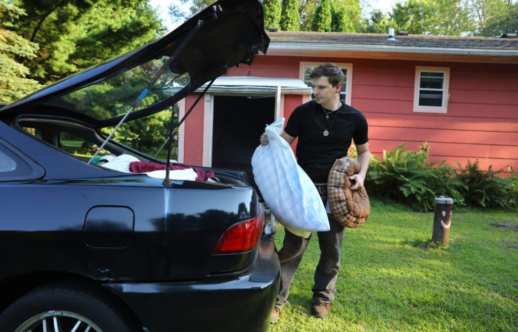 Cody McCormick, 29, packs belongings into his fiancé Breanna Kerssen's car in rural Monroe County on Aug. 1, as they prepare to move from his grandmother's house to an apartment in Sparta, Wis. McCormick faces ongoing difficulties with the GPS monitoring device he wears because of a conviction for a sex offense. Due to poor cell phone service at his grandmother's house, the GPS device would lose contact with the Madison-based monitoring center, resulting in false alerts. Photo by Coburn Dukehart / Wisconsin Center for Investigative Journalism.