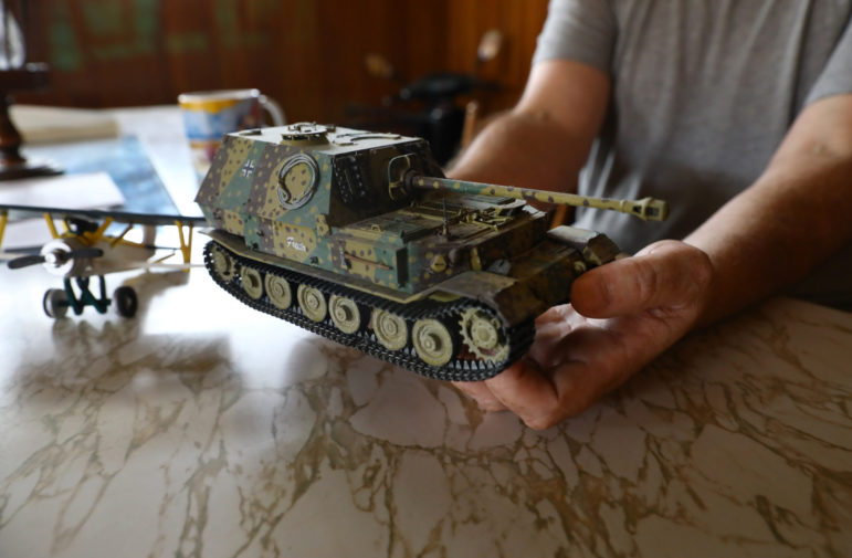 Steven Nichols, 48, shows off a model tank he built in his apartment in Whitehall, Wis. The model depicts a WWII-era German tank. Because he has few places to go during the day, he has taken up model building as a hobby. He says the GPS unit he wears is uncomfortable, causing abrasions to his leg and makes it hard to wear footwear, including winter boots. Photo by Coburn Dukehart / Wisconsin Center for Investigative Journalism.