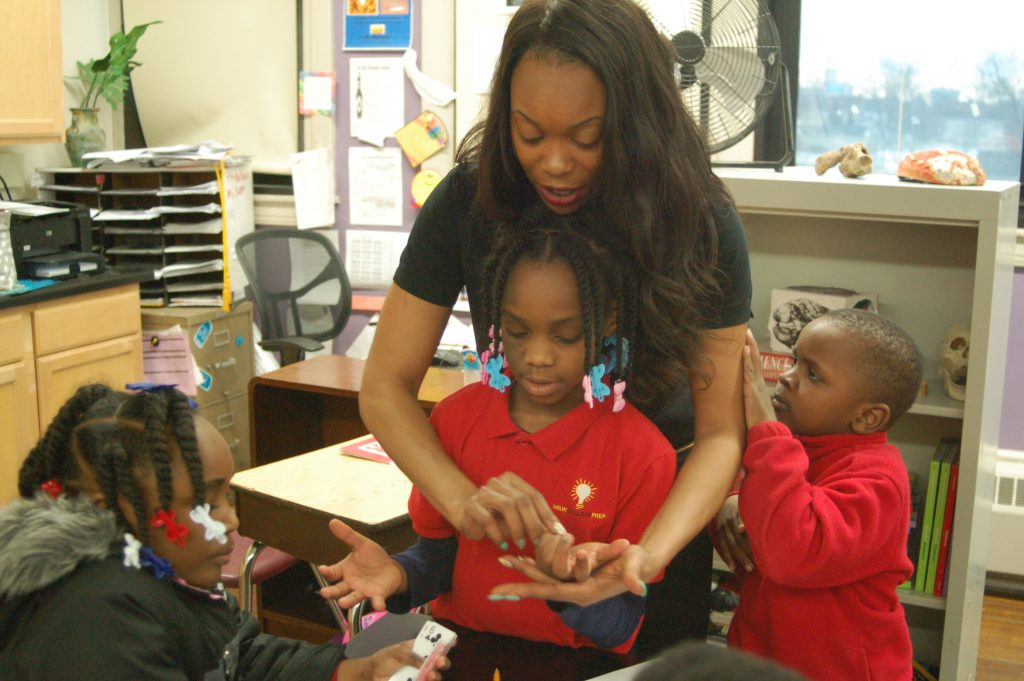 Teacher Portia Hunter helps third-grader Naomi Murphy learn to multiply and count by fives and 10s in the Young Einsteins math activity group. Photo by Andrea Waxman.