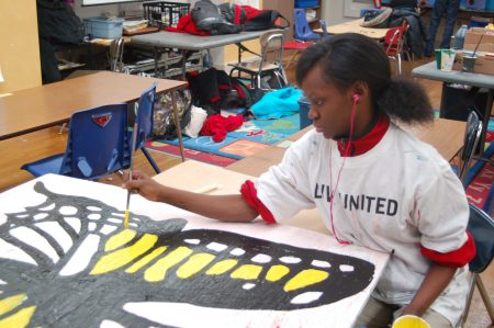 Zhakaria Murphy-Smith, a seventh-grader at Milwaukee College Prep's Lloyd Street campus, works on a section of a mural for the school's butterfly garden. Photo by Andrea Waxman.