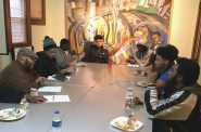 Terron Edwards (left, in cap), wellness coordinator at Walnut Way Conservation Corp., leads young men in a discussion. Photo by Dean Bibens.