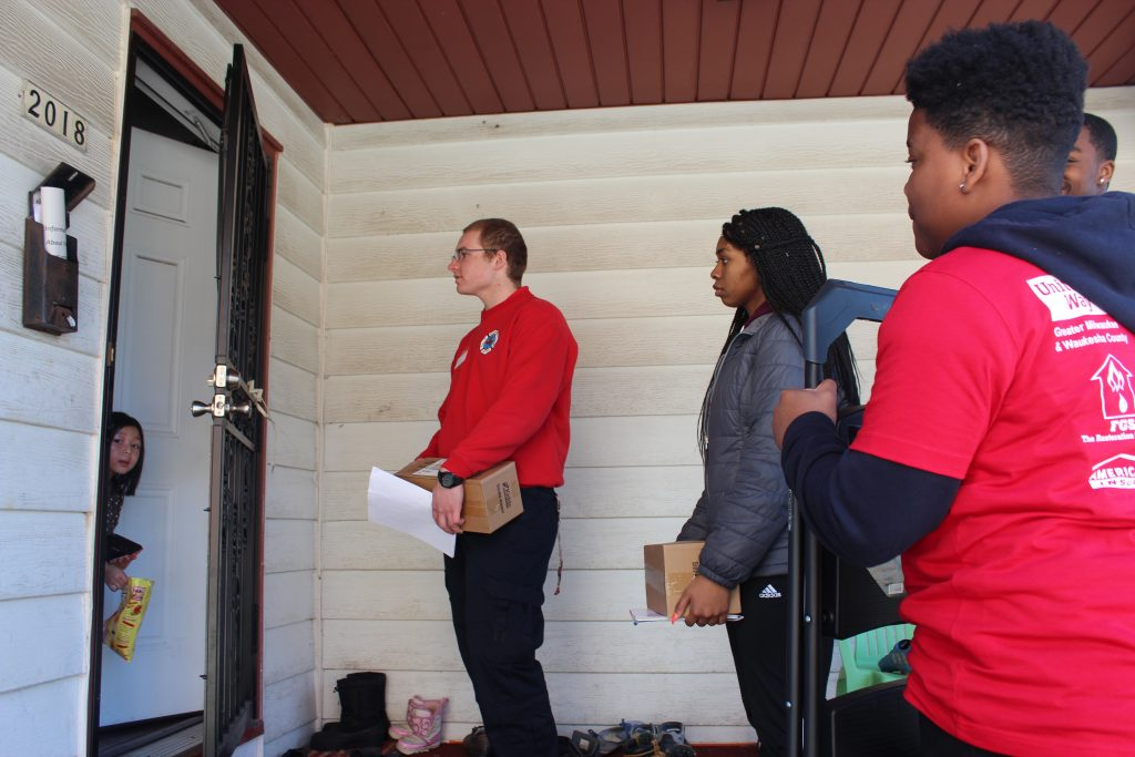 Milwaukee fire cadet Evan Jaksic (left) goes door to door with volunteers, asking if residents need their smoke alarms tested or installed. Photo Margaret Cannon.