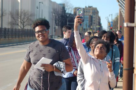 Jaylin Taylor (left) and Maya Garrett (right), two seniors from Messmer High School, march over the 16th street bridge. Photo by Rachel Kubik.