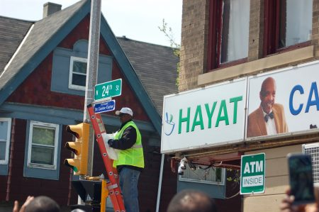 A public works employee unveils the new sign outside Carter Drug Store. Photo by Jenny Whidden.