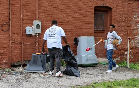 Two community members grab trash with pickers supplied by Home Depot and Keep Greater Milwaukee Beautiful. Photo by Mark Lisowski.