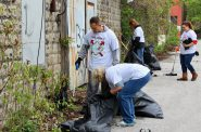 Volunteers scoop debris, including an abandoned collection of wine corks, into trash bags behind a building. Photo by Mark Lisowski.
