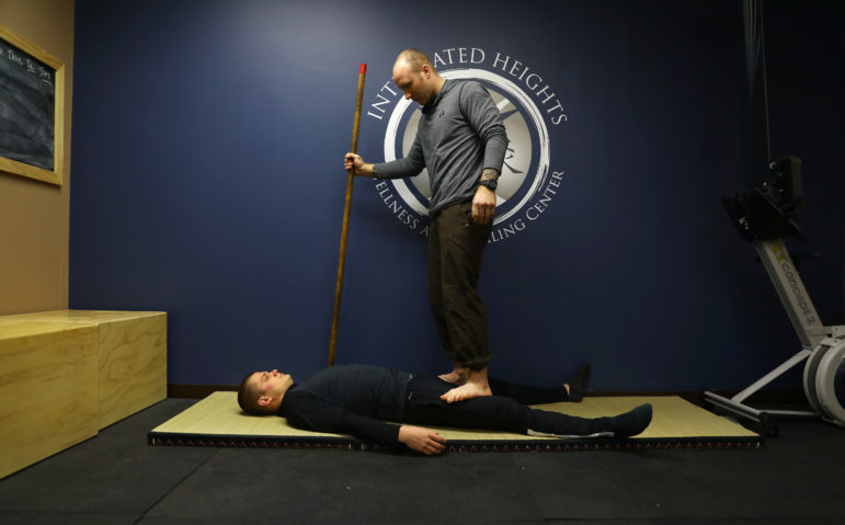 Former University of Wisconsin linebacker Tony Megna left football after suffering severe, repeated headaches. Now he runs Integrated Heights Wellness and Healing Center in Mount Pleasant, Wis., which offers various services such as injury recovery, acupuncture, massage and traditional Eastern medicine. Here Megna demonstrates his techniques on Connor Flannery, a semi-pro football player with the Racine Raiders. Photo by Coburn Dukehart / Wisconsin Center for Investigative Journalism.