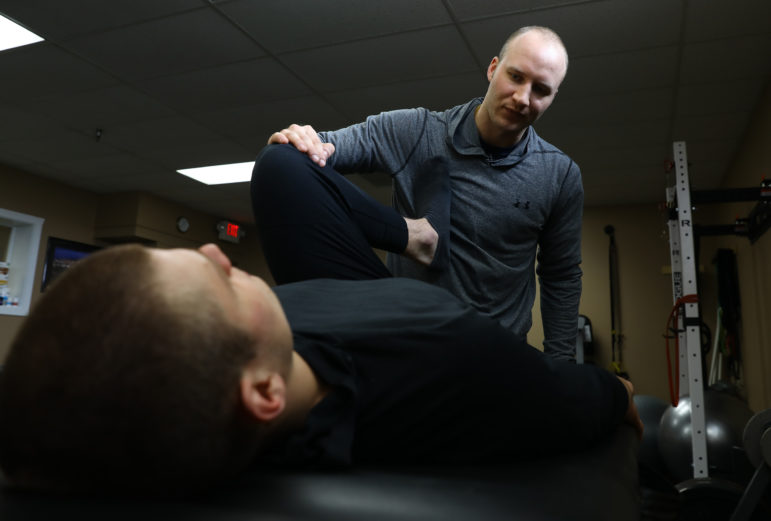 Tony Megna now runs Integrated Heights Wellness and Healing Center in Mount Pleasant, Wis. Here he works with Connor Flannery, a semi-pro football player with the Racine Raiders. Photo by Coburn Dukehart / Wisconsin Center for Investigative Journalism.