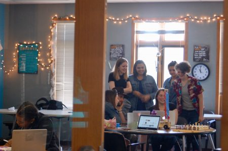 Students gather around a laptop in one of the school's main classrooms to view a project. Photo by Jenny Whidden.