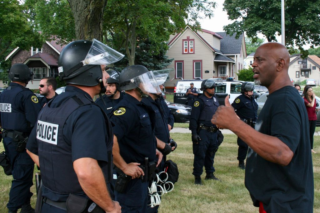 Officers talk to a man in the Sherman Park neighborhood during the August 2016 unrest that followed the police-involved shooting of Sylville K. Smith. Photo by Jabril Faraj.
