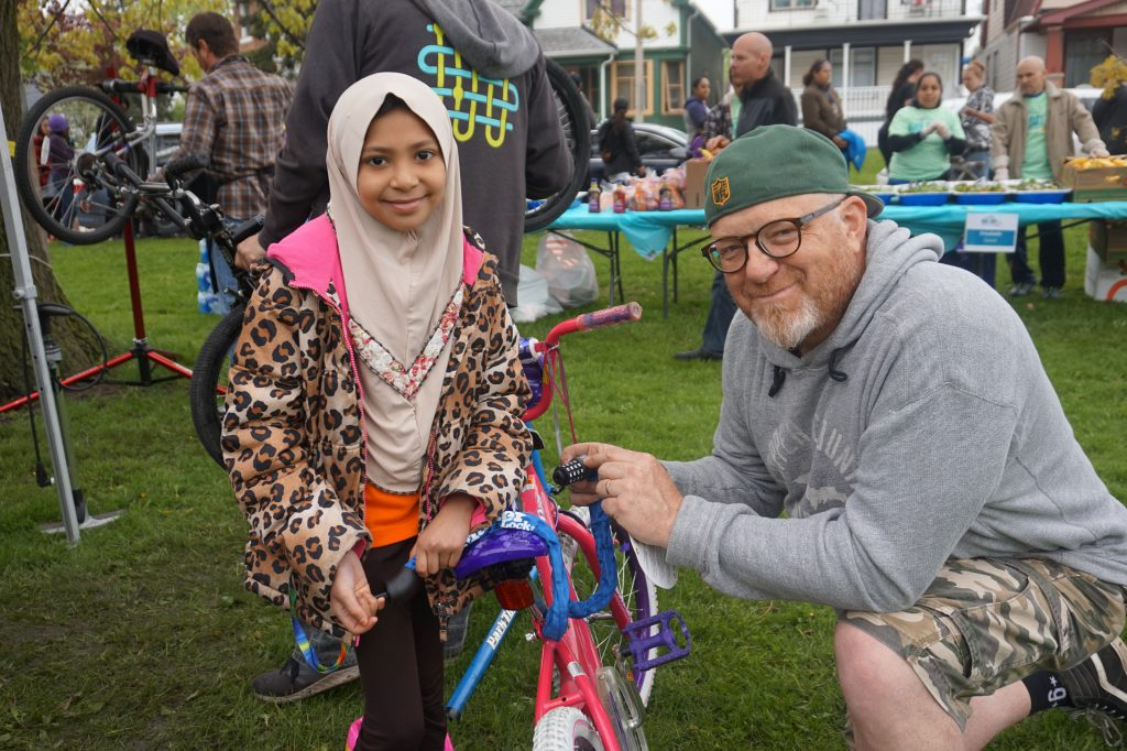 Rakel Ruida, 11, smiles as her new bike receives a tune-up from a Bike Day volunteer. Photo by Donna Sarkar.
