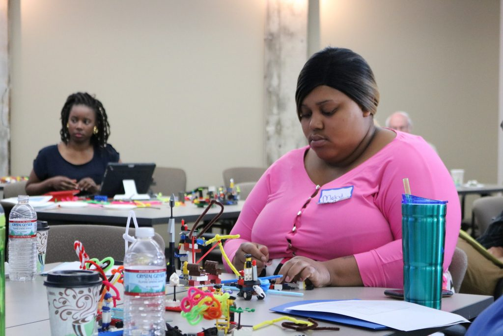 Melody McCurtis, a community organizer at Metcalfe Park Community Bridges, assembles Legos, which were scattered on each table at Data Day. Photo by Sophie Bolich.