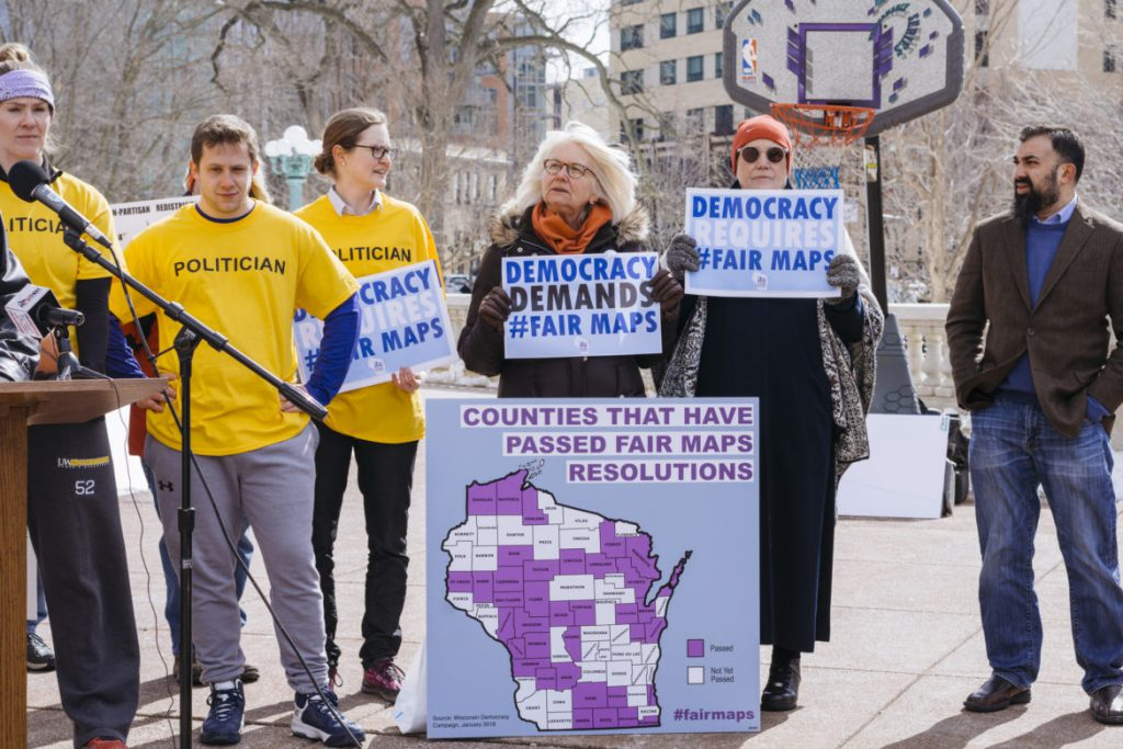 Marla Stephens, center, and Kris Lennon, center right, attend Maps Madness: Voters vs. Politicians, a March 7, 2018 rally organized by the Wisconsin Fair Maps Coalition held outside the Wisconsin state Capitol. The rally was aimed at pressuring lawmakers to hold a special session to enact a nonpartisan redistricting system. Stephens, a former candidate for state Supreme Court justice, says she believes her vote has been diluted by redistricting in the Milwaukee area. Photo by Cameron Smith/Wisconsin Center for Investigative Journalism.