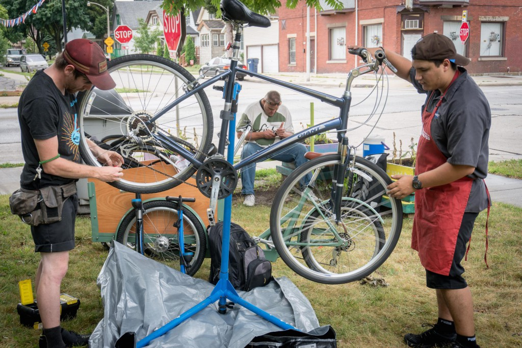 Brennon and Jean repair a bike at Burnham Park while the owner waits with a neighbor.