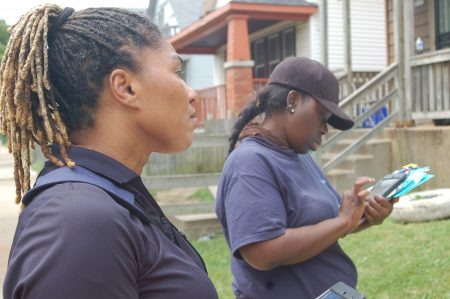 Canvassers Marsha Ashley (left) and Orean Harper use tablets to keep track of the doors they have knocked on. Photo by Jenny Whidde.