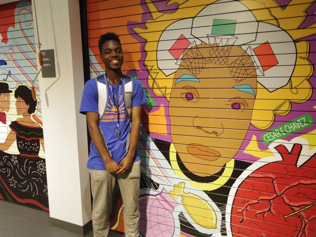 Milwaukee Public Library teen intern Alvin Watts stands in front of his design, which was inspired by his cultural roots in Milwaukee. Photo by Robyn Di Giacinto.