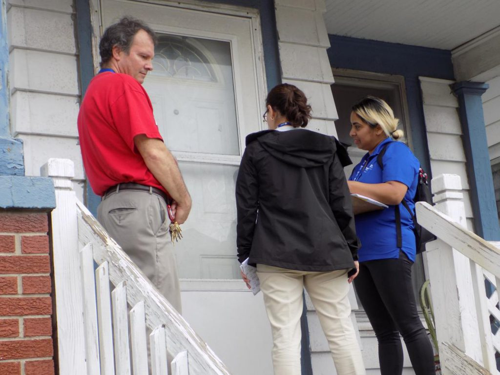U.S. Grant School Principal Tom Bruno, left, goes door-to-door with canvassers in efforts to recruit students into Milwaukee Public Schools. Photo by Ximena Conde/WPR.