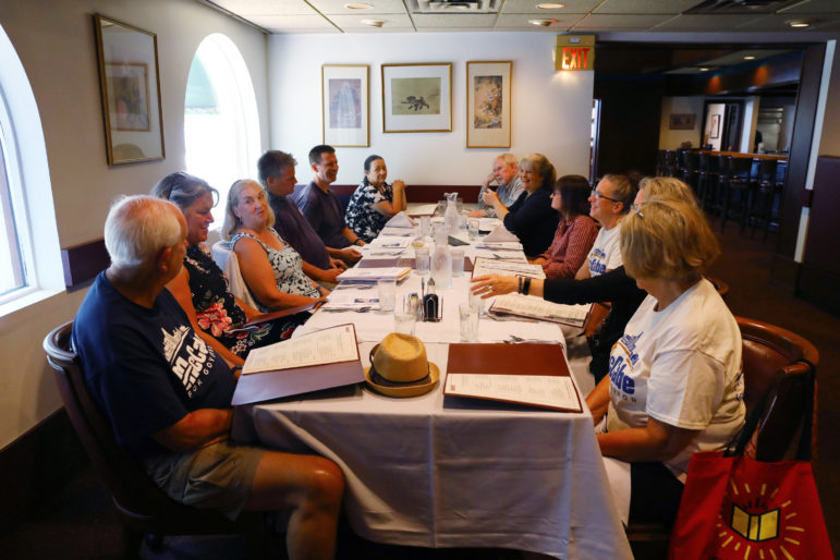 "The Wisconsin Election Integrity group meets at the Imperial Garden restaurant in Middleton, Wisconsin on July 13. The group, which advocates for ""appropriate use and management of election technology"" to secure Wisconsin's elections, is coordinated by Karen McKim. Seated, clockwise from top right, are: Al Sulzer, Karen McKim, Liz Whitlock, Alice Schneiderman, Maggie Thomas, Susan Dopp, Ron Biendseil, Sue Trace, Rebecca Alwin, Brad Geyer, Andy Bersch and Christine McDonough. Photo by Coburn Dukehart / Wisconsin Center for Investigative Journalism."