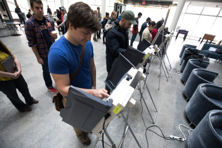 Students participate in a voting demonstration at the University of Michigan in 2018, organized by J. Alex Halderman, director of the University of Michigan's Center for Computer Security and Society. Students were asked to pick which school was better — Michigan or Ohio State. From his office computer, Halderman remotely altered the tally, making Ohio State the winner in a race where the majority of voters picked Michigan. Photo courtesy of the University of Michigan Computer Science and Engineering Department.