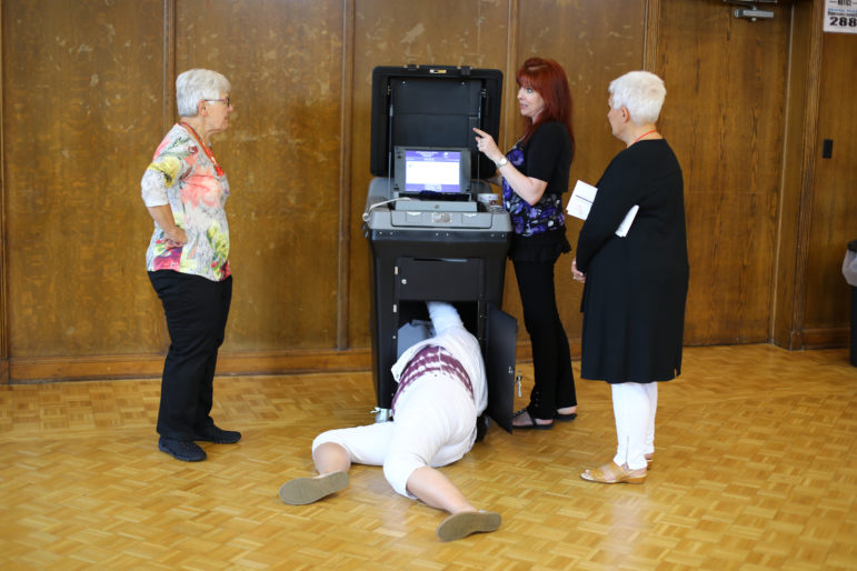 Julie Routhieaux, administrative specialist for the village of Little Chute, Wisconsin, climbs into the DS200 scanner and tabulator voting machine to clear a paper jam caused by a stuck absentee ballot. Also seen are Rita Mollen, chief election inspector, left, Municipal Clerk Laurie Decker, center, and Deborah Hermsen, election-chief-in-training, right. Decker said that the paper jam, or the act of clearing it, had no effect on election security. Photo by Coburn Dukehart / Wisconsin Center for Investigative Journalism.