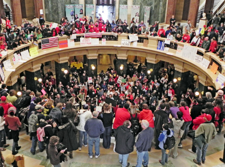 Union workers, teachers and other protesters showed up for weeks at Wisconsin's Capitol building in protest of Gov. Scott Walker's budget repair bill, later known as Act 10, which reduced public sector union workers' benefits and eliminated collective bargaining rights for many of them. Photo by Richard Hurd. (CC BY 2.0)