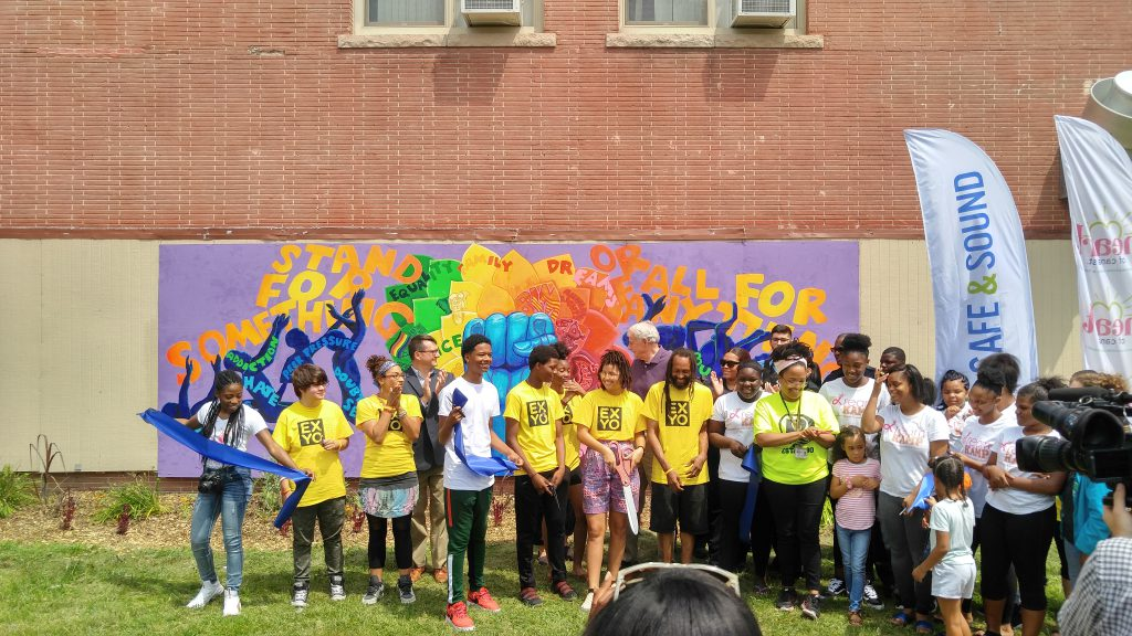 Youth from Express Yourself MKE unveil their new mural at Running Rebels Community Organization. Photo by Zach Komassa.