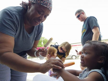 Near West Side resident Annie Harrell shares a sweet treat with her grandchild, KJ. Photo by Robyn Di Giacinto/NNS.