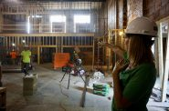 Juli Kaufmann points out where new shops and seating will be inside the Sherman Phoenix. Photo by Abby Ng/NNS.
