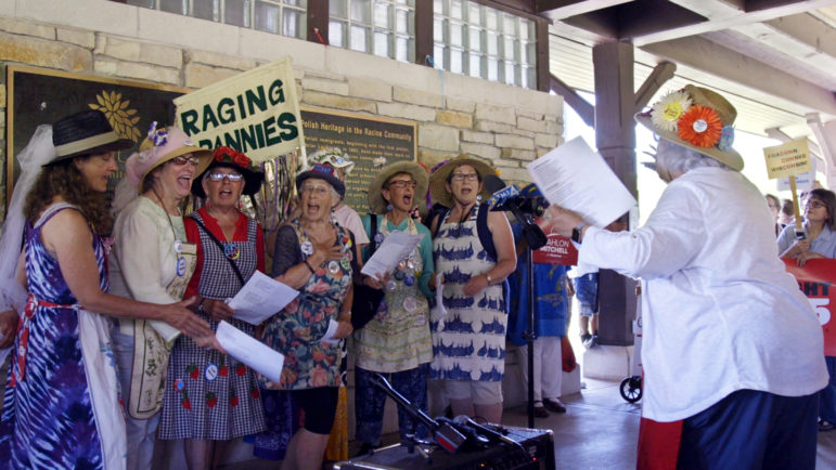"Demonstrators, including the Raging Grannies singing group, gather at Smolenski Park in Mount Pleasant, Wis., on June 28, 2018 to protest the groundbreaking for the Foxconn manufacturing plant, which will receive more than $4 billion in state and local taxpayer subsidies. At far right in the line is activist Sheila Plotkin, whose group, We the Irrelevant, has documented instances in which the Legislature has approved bills over strong public opposition. ""Most people believe government no longer represents the people,"" Plotkin said. ""It represents campaign donors, special interests, the wealthy."" Photo courtesy of Jim Cricchi / Twelve Letter Films."