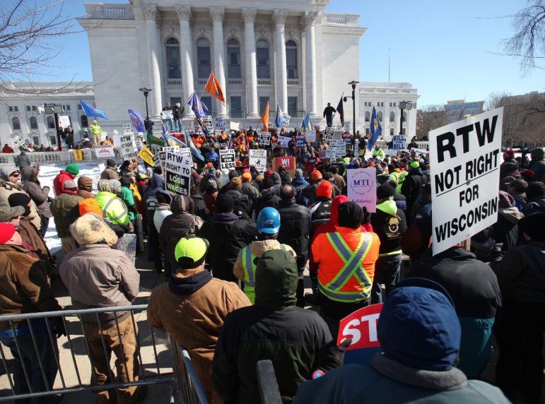 Protesters listen to speakers at a rally against the proposed Right to Work legislation at the state Capitol in Madison, Wis., on Mar. 5, 2015. Passage of the bill was among the 11 percent of all bills fast-tracked during the 2015-16 legislative session, a Wisconsin Center for Investigative Journalism analysis showed. It took just 14 days from introduction to Gov. Scott Walker's signature. Walker had earlier stated he had no plans to adopt such a measure. Photo by Mike DeVries / The Capital Times.