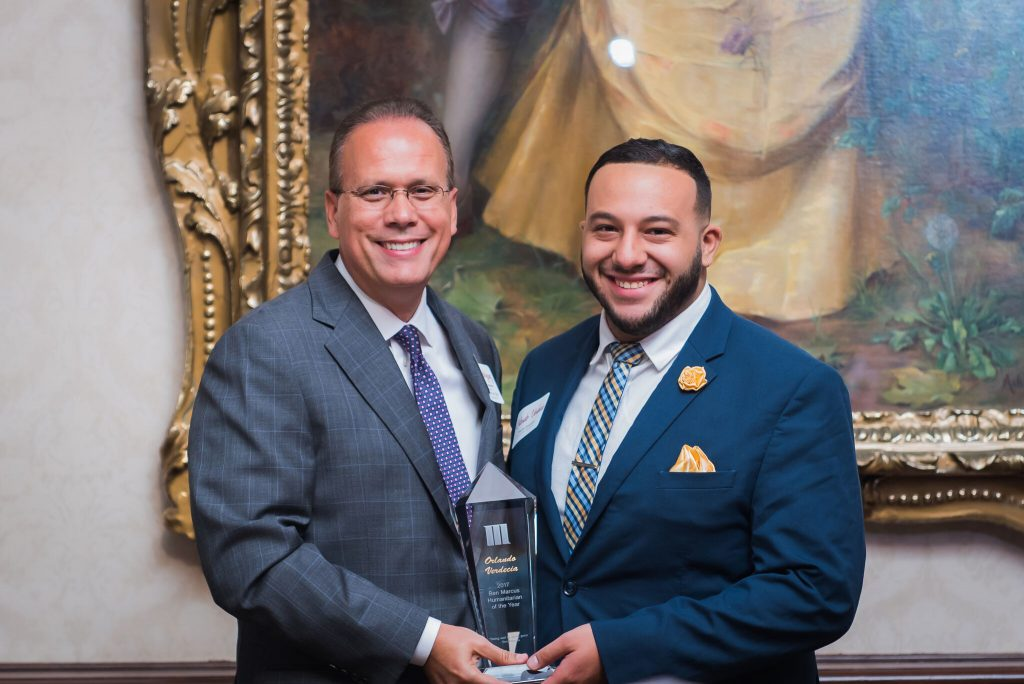 Orlando Verdecia [R] receiving his honor from Rolando Rodriguez, executive vice president of The Marcus Corporation and chairman, president and chief executive officer of Marcus Theatres. Photo courtesy of The Marcus Corporation.