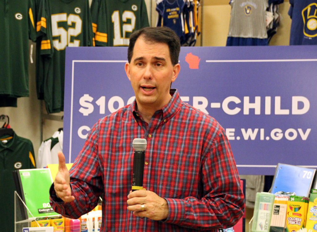 Elected officials like Gov. Scott Walker, photographed touting his tax policies at a Shopko in Sussex on May 15, 2018, cannot use state resources for campaign purposes, but the rules are less clear on how they should divide up their time between their roles as officeholder and candidate. Photo by Shawn Johnson/Wisconsin Public Radio.
