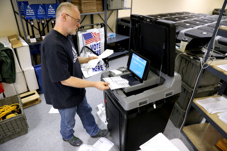 Certified Municipal Clerk Thomas Lund heads up a public test of election equipment in Madison, Wis., ahead of the Aug. 14, primary. A group of paid staff and volunteers test all the voting machines by running ballots with all voting scenarios for that ballot, and for each candidate, through the machines and making sure they tally them correctly. Photo by Coburn Dukehart / Wisconsin Center for Investigative Journalism.