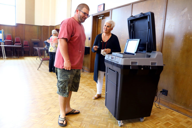 Brad Pamperin talks with Deborah Hermsen, an election chief-in-training, during voting at the village hall in Little Chute, Wis., for a special election in the 1st Senate District on June 12, 2018. The village had retired an older style of voting machine for the newer DS200 scanner and tabulator. Officials also were using a new ExpressVote machine for electronic voting. State officials insist that Wisconsin's elections infrastructure is secure because, among other safeguards, voting machines are not connected to the internet and each vote is backed by a paper ballot to verify results. Photo by Coburn Dukehart / Wisconsin Center for Investigative Journalism.