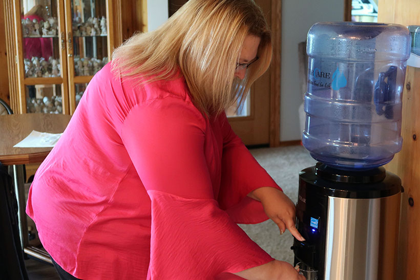 Erika Balza fills up a glass of water in her Kewaunee County home. She doesn't use tap water for drinking or cooking, optin instead to use water from her water cooler. Photo by Danielle Kaeding/WPR.