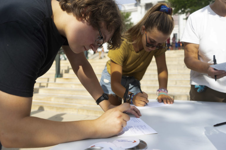 Frances Bartolutti, 19, at left, and Talia Glass, 15, pledge to vote at a table run by political advocacy group NextGen America at the Wisconsin State Capitol on Aug. 4, 2018. Bartolutti says she was looking forward to voting in her first Senate and gubernatorial race. A government study found that voter ID requirements such as Wisconsin's can lead to lower voter turnout among young people. Photo by Belle Lin / Wisconsin Center for Investigative Journalism.