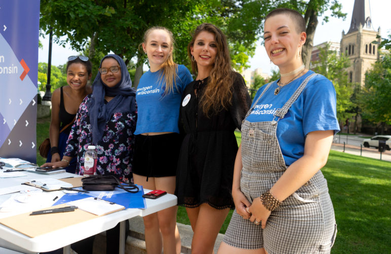 From left, Lucy Smith, 19, Nada Elmikashfi, 22, Caroline Bergman, 19, and Izzy Owca, 19, and Simone Williams, 20, of the political advocacy group NextGen America urge young voters to sign cards to pledge to vote at the Wisconsin State Capitol on Aug. 4, 2018. Wisconsin requires a photo ID for voting, which a government study found can lead to lower turnout among young voters. Photo by Belle Lin / Wisconsin Center for Investigative Journalism.