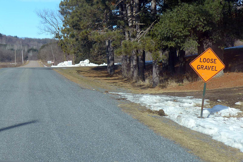 This March 2017 photo shows a sign warning drivers in Northfield, Wis. of loose gravel ahead. The town has turned 12 miles of road from pavement to gravel. Shawn Johnson/WPR.