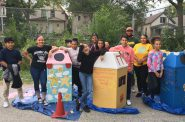Myron Edwards, District 2 youth organizer for Safe & Sound, and young people from Journey House pose with their 'beautiful garbage' receptacles. Photo by Myron Edwards, courtesy of Safe & Sound/NNS.