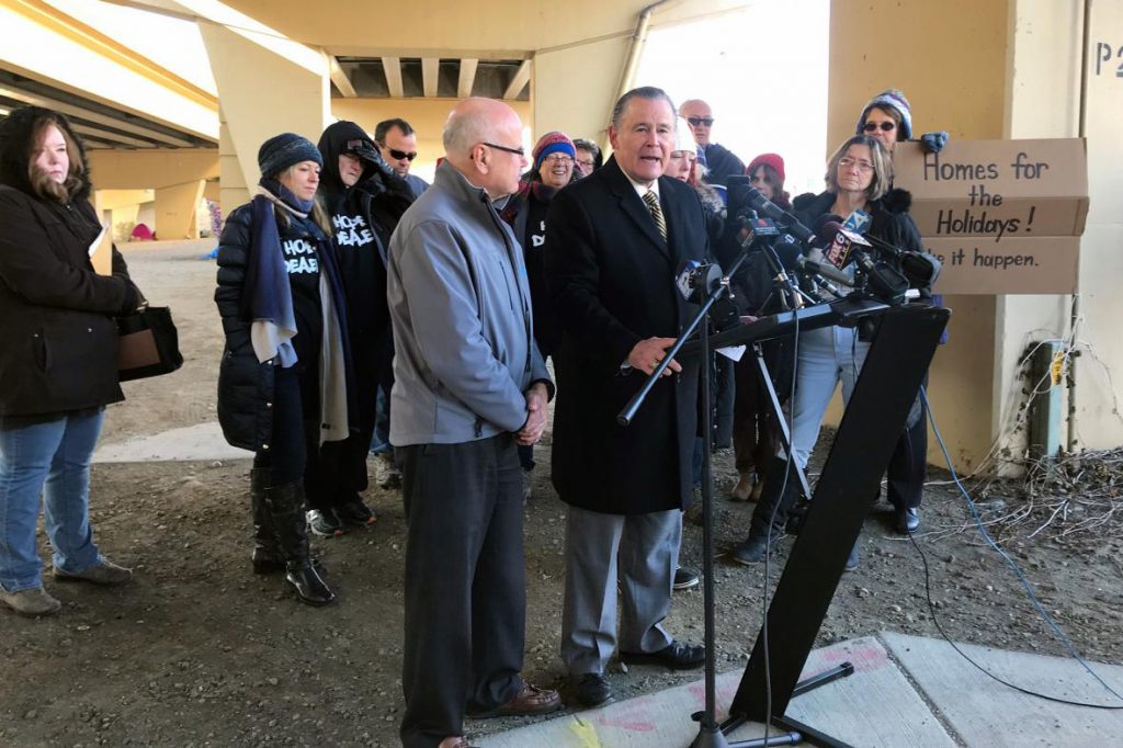 Milwaukee Alderman Bob Donovan, right, speaks to reporters on Tuesday, Nov. 20, 2018, under one of a dozen homeless encampments under the city's viaducts. Photo by Corri Hess/WPR.