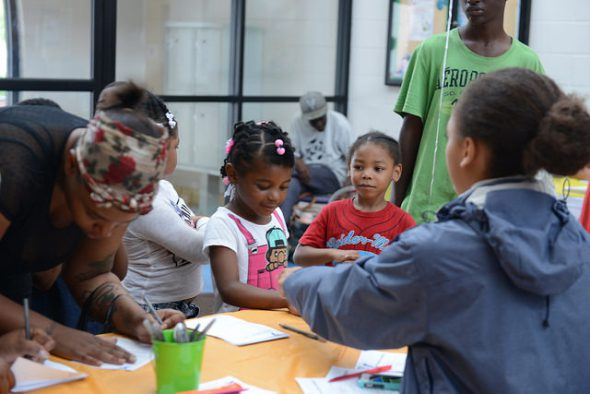 A mom registers her children at the Northside YMCA Healthy Kids Day. Photo by Sue Vliet/NNS.