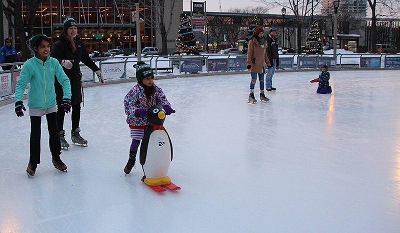 Young girl using a Polar Pal for extra support when skating at Slice of Ice in Red Arrow Park. The skating season opens with free skate rentals Dec. 12, from 4–6 p.m. Photo from Milwaukee County Parks.