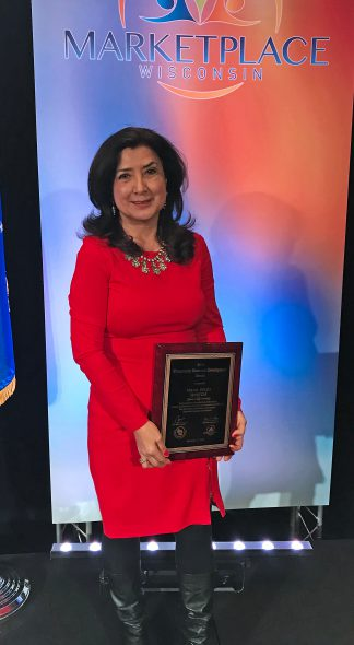 Maria Watts receiving Community Economic Development award at the 2018 Wisconsin Marketplace event. Photo courtesy of WHEDA.