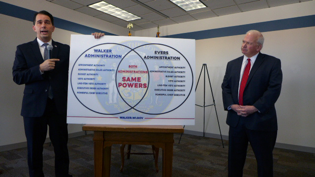 Gov. Scott Walker, left, and state Sen. Scott Fitzgerald, R-Juneau, right, next to a venn diagram and Walker says shows the powers governors have after he signed several bills from the lame-duck session Friday, Dec. 14, 2018, in Green Bay, Wisconsin. Photo by Patty Murray/WPR.